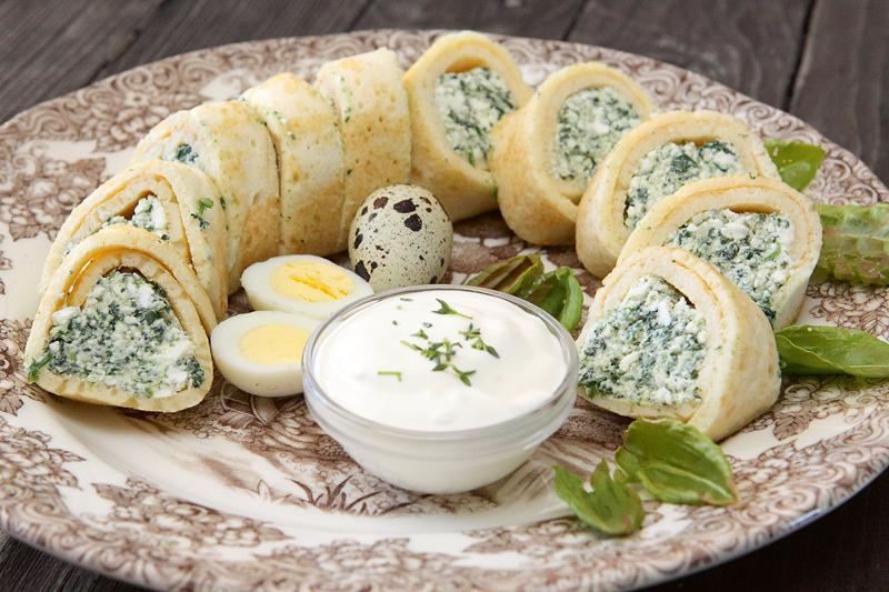 Pankūkas ar svaigā siera masas pildījumu un mērci. Spinātus un skābenes sagriež un apcep sviestā, pievienojot ķiplokus, sāli un piparus. Tad zaļumus sajauc ar svaigā siera un biezpiena masu, pilda pankūkās, tās satin un sagriež ripiņās. Pasniedz ar mērci, kas gatavota no skābā krējuma, majonēzes, graudu sinepēm, sarīvētiem marinētiem gurķiem un pipariem. Rotā ar svaigām skābeņu lapiņām un vārītām paipalu olām.