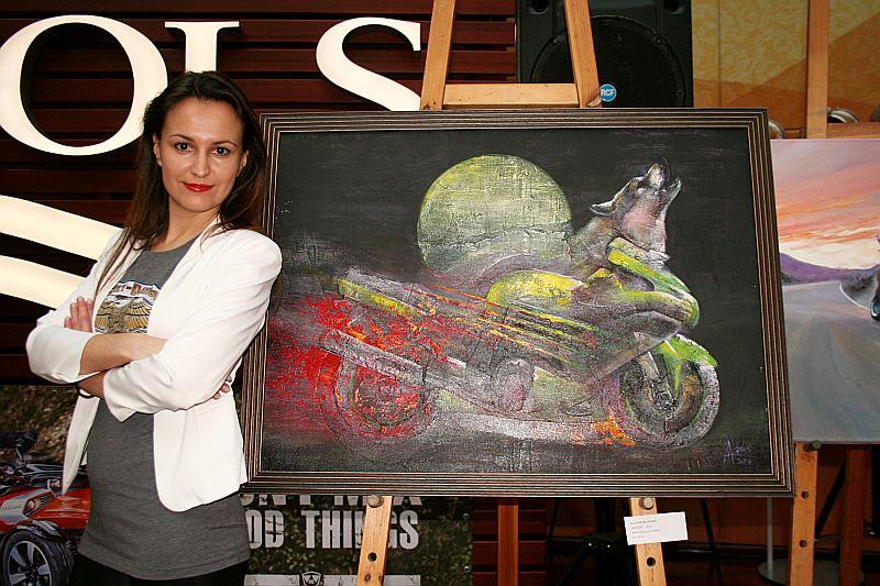 """Tirdzniecības centrā """"Mols"""" apskatāmas arī gleznas ar moto tematiku. Māksliniece Alla Dzevaltovska pie savas gleznas """"Vilks ZZR"""". ZZR tāpēc, ka viņas vīram ir motocikls """"Kawasaki ZZR"""", uz kura māksliniece ir otrā vadītāja jeb pasažiere, bet vilks tāpēc, ka tā tēls atbilstot motocikla dvēselei. Alla pati ikdienā brauc ar 125 cm3 čoperīti."""