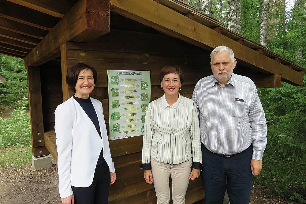 """VVD pārstāve Aina Stašāne (no kreisās), DAP ģenerāldirektore Sandra Bērziņa un SIA ZAAO valdes priekšsēdētājs Aivars Sirmais tūristu apmetnes zonā pie Sietiņieža izvietoja pirmo """"Lasi skaļi un dzīvo zaļi!"""" plakātu."""