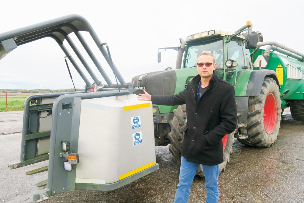 """""""Lauku Agro"""" projekt vadītājs Gints Jakubovskis pie sērskābes tvertnes. No tās skābi sūknē uz maisītāju mucas aizmugurē."""