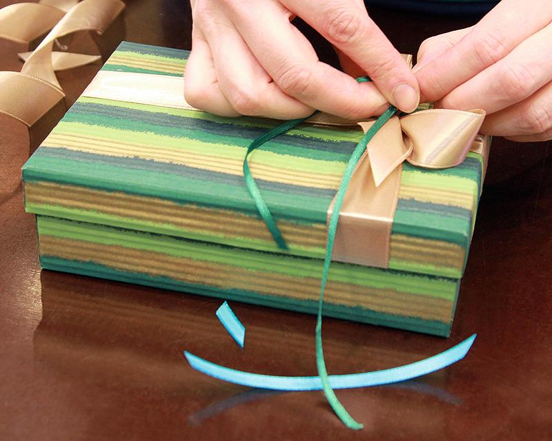 Ekonomiskais variants. Atlasa lentīte nav obligāti jāsien apkārt dāvanu kastei. Lentīti nogriež kastītes vāka platumā ar 2–4 centimetru rezervi, stingri nostiepj pāri vākam un lentītes galus pielīmē vāka iekšpusē. Tad veido pušķi, ko pielīmē vai piešuj pie pielīmētās atlasa lentes.
