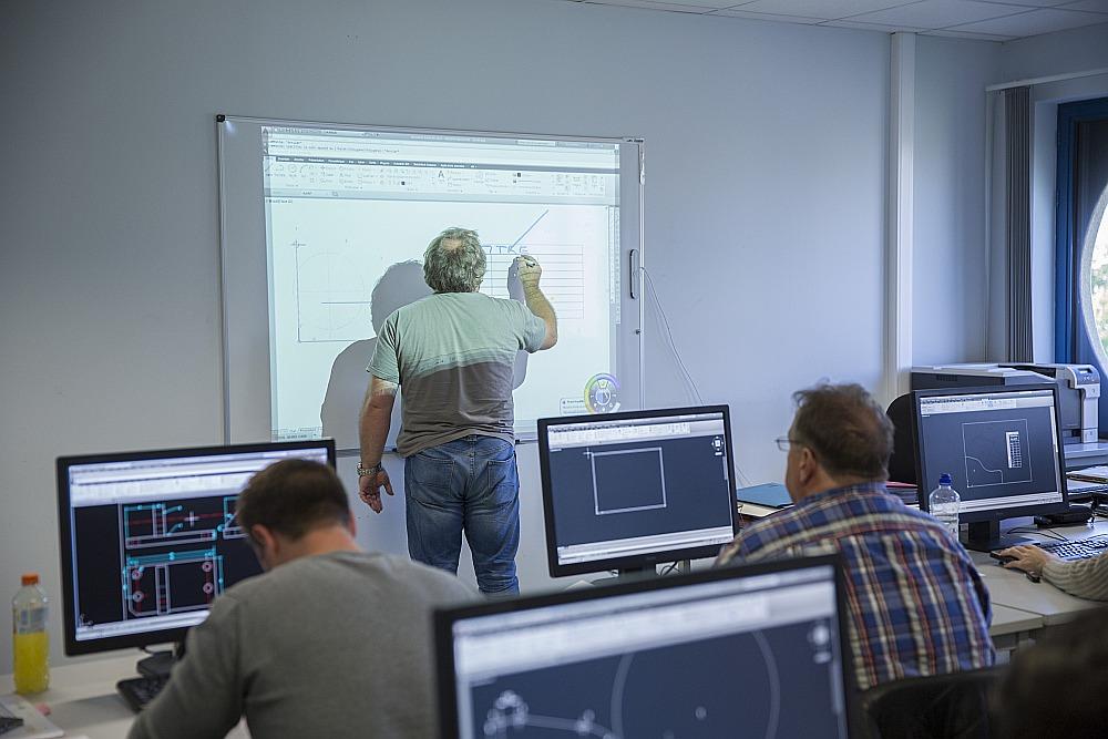 """Bezdarbnieku profesionālās apmācības kursi """"TechnoCampus"""" Goseljē, Beļģijā, kuros pasniedzējs palīdz apgūt datordizaina programmatūru."""