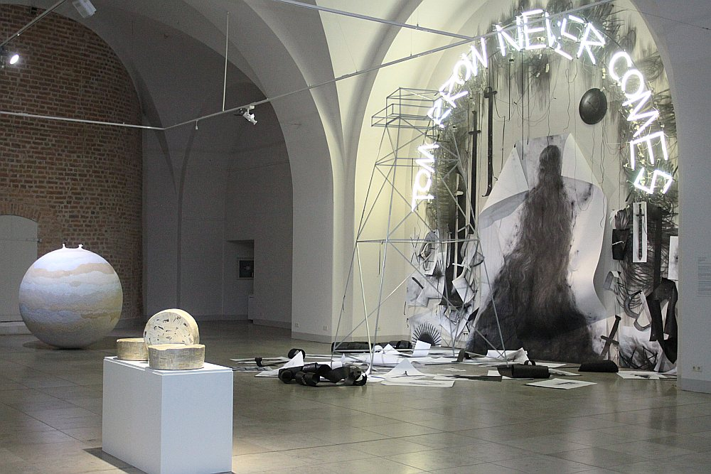 """Pašā ekspozīcijas sākumā ar lieliem halogēna burtiem skatītājam virsū spīd Artūra Virtmaņa instalācijas vēstījums, ka """"Tomorrow never comes"""" (""""Nākotne nekad neatnāks"""")."""