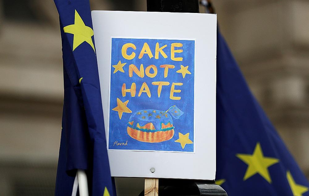 """Protestētāji otrdien ar plakātu """"Cake not hate"""" (vārdu spēle ar komatiem """"Kūka ne naids"""", pēc analoģijas ar """"Sodīt nedrīkst apžēlot"""") pie britu premjera rezidences."""