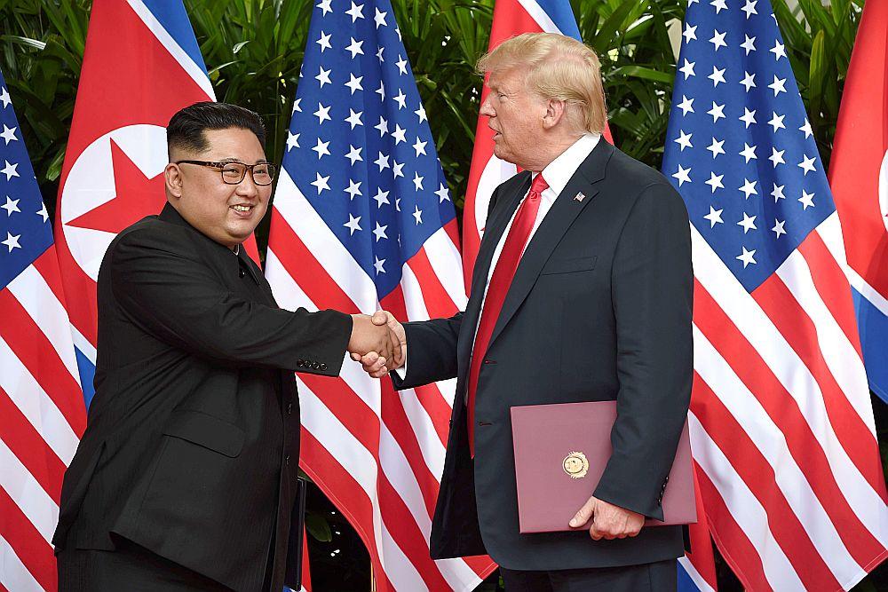 ASV prezidents Donalds Tramps un Ziemeļkorejas līderis Kims Čenuns sarokojas pēc kopīgā dokumenta parakstīšanas samitā Singapūrā jūnijā