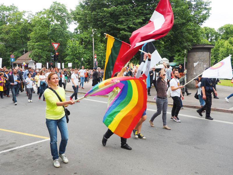 """""""Eiro praidā"""" Rīgā 2015. gadā. Amerikāņa Gilberta Beikera 1978. gadā radītais astoņu krāsu karogs kļuvis par LGBT kustības un tās atbalstītāju simbolu. Sarkanā krāsa simbolizē dzīvi, oranžā – dziedināšanu, dzeltenā – saules gaismu, zaļā – dabu, tirkīza – mākslu, indigo – rāmumu, rozā – seksualitāti  un violetā – garu."""