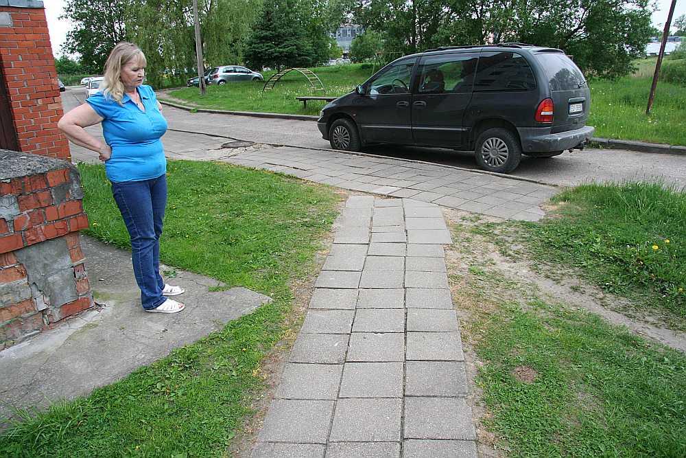 Mājas vecākā Raisa Dubeņecka uz mājas sabojātās aizsargplāksnes pie gājēju celiņa, kas jau sakārtots.
