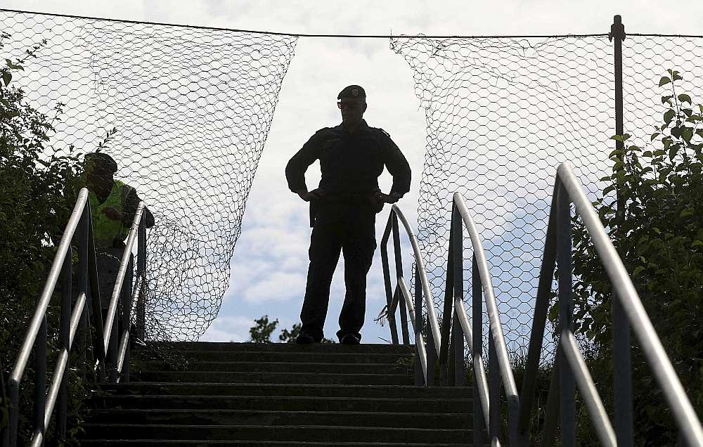 Austrijas policijas virsnieks robežapsardzības mācībās Špīlfeldā 26. jūnijā pie žoga uz Austrijas robežas ar Slovēniju.