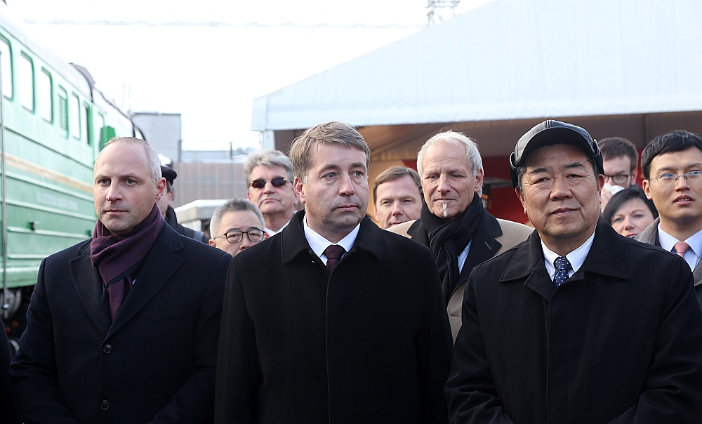 """Toreiz, 2016. gada 5. novembrī, Satiksmes ministrijas valsts sekretārs Kaspars Ozoliņš (no kreisās), satiksmes ministrs Uldis Augulis un Ķīnas Nacionālās attīstības un reformu komisijas direktora vietnieks He Lifengs testa konteinervilcienu """"Jivu–Rīga"""" sagaidīja Rīgas Centrālajā stacijā. Tagad pirmie divi brauca uz Ķīnu ar nepārspētiem šo testu rezultātiem."""