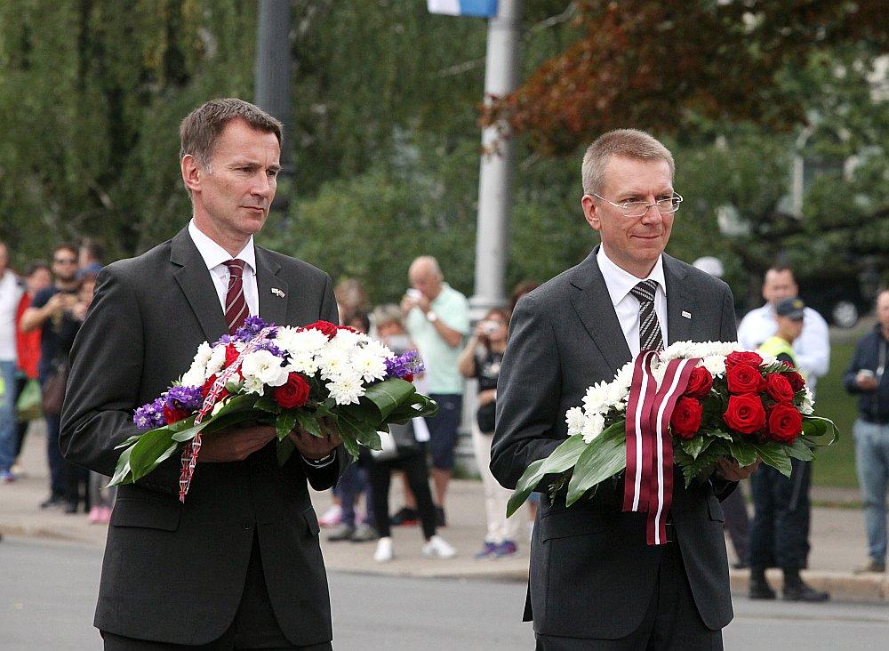 Apvienotās Karalistes ārlietu ministrs Džeremijs Hants (no kreisās) kopā ar Latvijas ārlietu ministru Edgaru Rinkēviču nolika ziedus pie Brīvības pieminekļa.