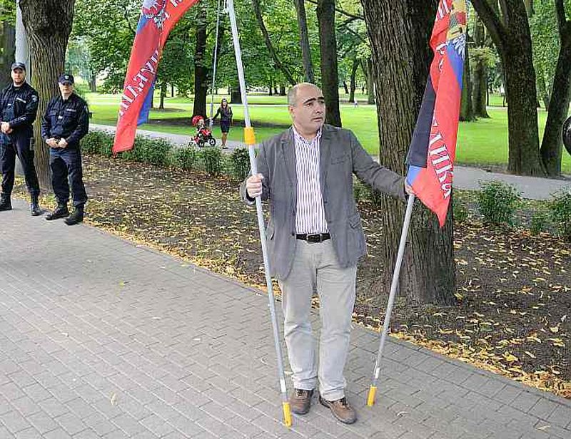 """Aizturētais ždanokietis Iļja Kozirevs 2014. gadā Latvijas Krievu savienības rīkotā piketā iepretim Ukrainas vēstniecībai tur pašpasludinātās """"Doņeckas tautas republikas"""" karogu."""