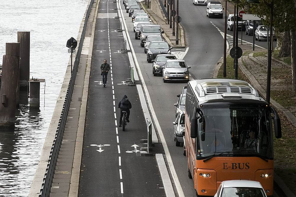 Riteņbraucēji virzās pa veloceliņu gar Sēnas upi.