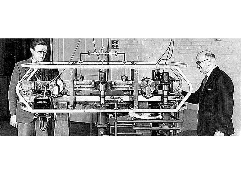 Luijs Esens (pa labi) pie pirmā atompulksteņa.