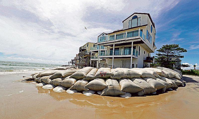 Ar smilšu maisiem nostiprināts nams Ziemeļkarolīnas piekrastē pirms vētras.