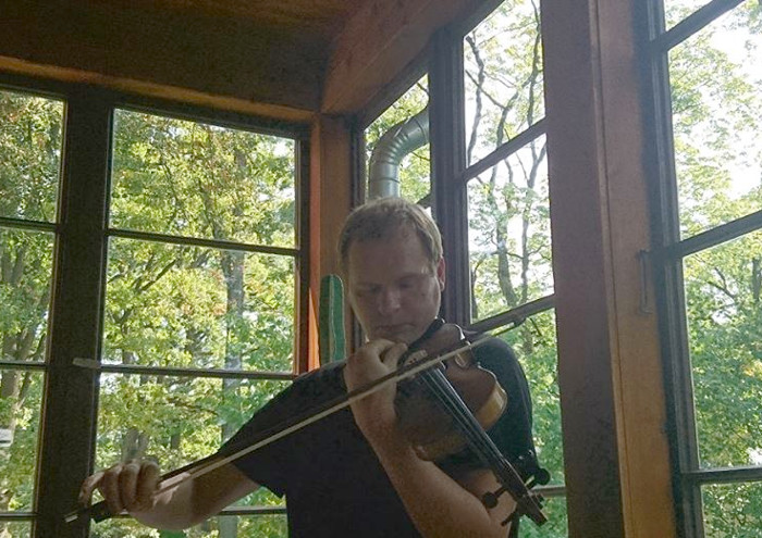 Restaurators Ingars Rancevičs Akuratera mājas verandā demonstrē restaurētās vijoles skaņu.