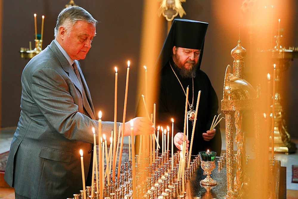 """Bijušais """"Krievijas dzelzceļu"""" priekšnieks, """"pareizticīgais čekists"""" un apustuļa Andreja fonda aizbildņu padomes priekšsēdētājs Vladimirs Jakuņins (no kreisās) aizdedz svecītes Krievijas pareizticīgo baznīcas Svētās Trīsvienības katedrālē Jeruzalemē."""