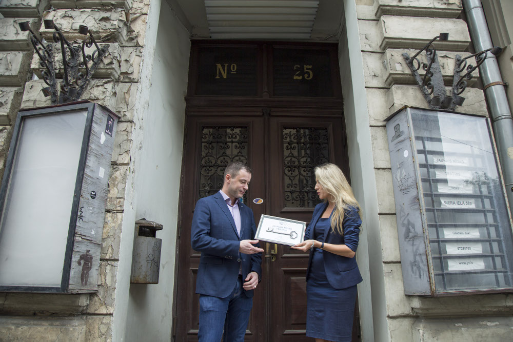 """VAS """"Valsts nekustamie īpašumi"""" valdes locekle Kitija Gruškevica simboliski nodod atslēgas būvniekam- pilnsabiedrības """"RERE Būve 1"""" valdes priekšsēdētājam Valdiim Kokam."""