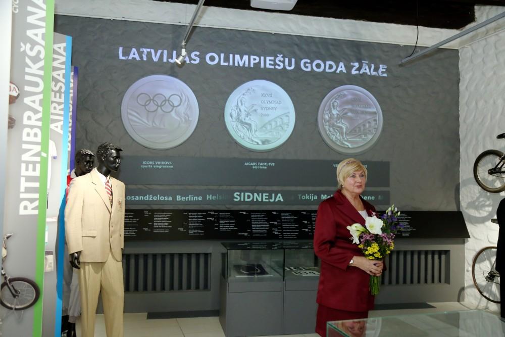 Latvijas Sporta muzeja direktore Agra Brūne atklāj Latvijas olimpiešu goda zāli.