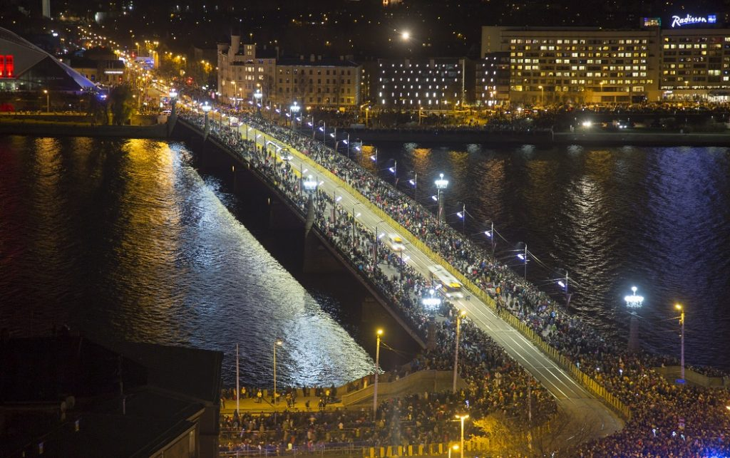 """Cilvēki 11.novembra krastmalā un apkārtnē pirms Latvijas simtgades jubilejai veltītā gaismas uzveduma """"Saules mūžs""""."""