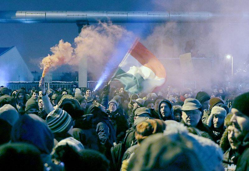 """Demonstrācija Budapeštā pie valsts televīzijas ēkas pret premjerministra Viktora Orbāna valdības pieņemto """"vergu darba likumu""""."""