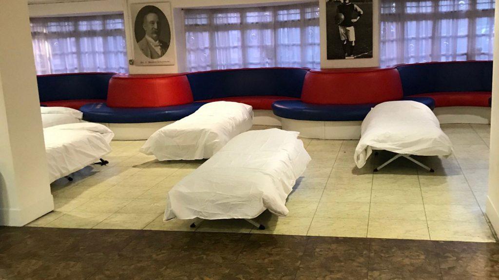 """Gultas bezpajumtniekiem angļu futbola kluba """"Crystal Palace"""" stadiona telpās."""