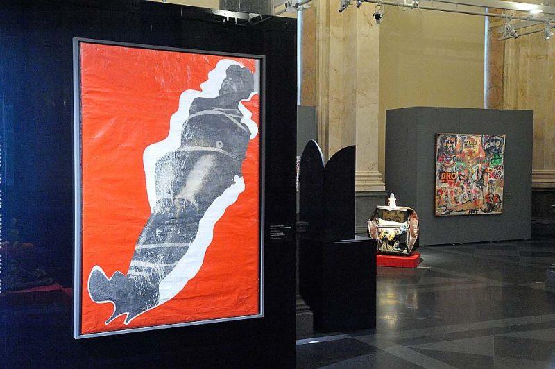 """Skats no izstādes. Priekšplānā Borisa Lurjē (1924–2008) darbs """"Mīlas sērija: sasaistītais uz sarkana fona"""". Ap 1963. Audekls. Fotoemulsija, akrils. Borisa Lurjē Mākslas fonda kolekcija, Ņujorka."""