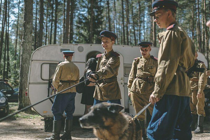 """Kadrs no LTV seriāla """"Sarkanais mežs"""" uzņemšanas – čekistu formas tērpos ģērbti aktieri gatavojas """"tīrīt"""" mežu, meklējot mežabrāļus. Uzņemts netālu no Ložmetējkalna."""