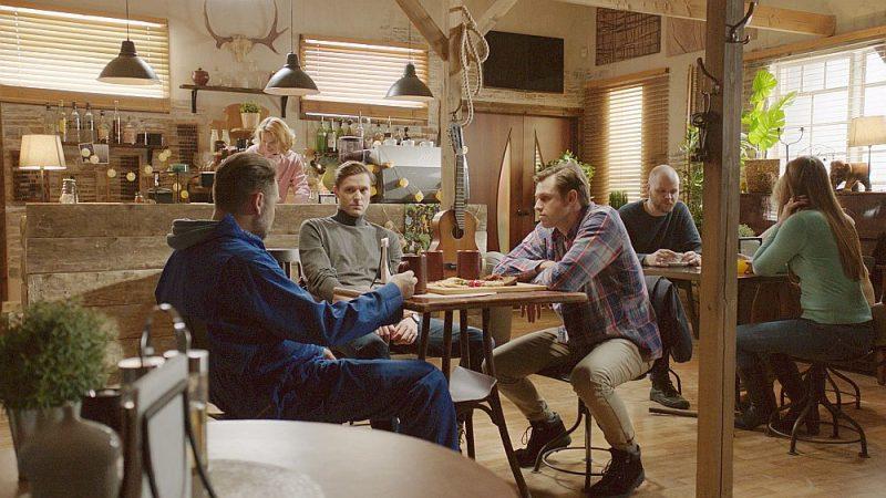 Daiņa Grūbes atveidotais galvenais varonis Dāvis Avots (otrais no kreisās) seriālā daudz laika pavada vietējā Skaistkalnu kafejnīcā, kopā ar draugu, vietējā radio dīdžeju Kārli (Edgars Samītis, trešais no kreisās) dzerot alu.