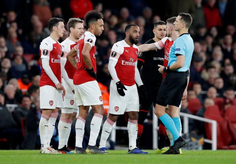 """Londonas """"Arsenal"""" kluba zvaigznes cenšas diskutēt ar latviešu tiesnesi Andri Treimani."""