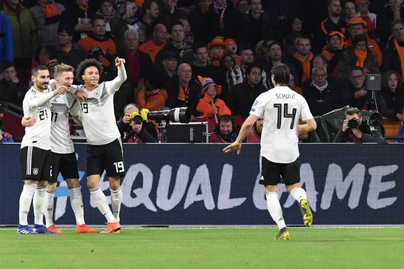 Vācijas futbola izlases spēlētāji priecājas par uzvaru.
