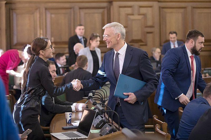 """Premjers Krišjānis Kariņš Saeimas sēdē sacīja: """"Latvija varētu būt pārtikusi ziemeļvalsts, kur cilvēki dzīvo drošībā, pārticībā – ir apmierināti ar dzīvi un laimīgi."""" Attēlā: premjers sasveicinās ar Saeimas deputāti Karinu Sprūdi (""""KPV LV"""")."""