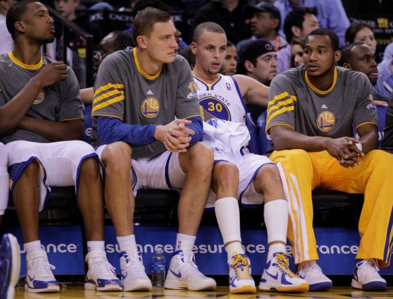 """NBA 2012.gada sezona – uz """"Warriors"""" rezervistu soliņa Andris Biedriņš (otrais no kreisās), bet blakus viņam Stefans Karijs (Nr.30)."""