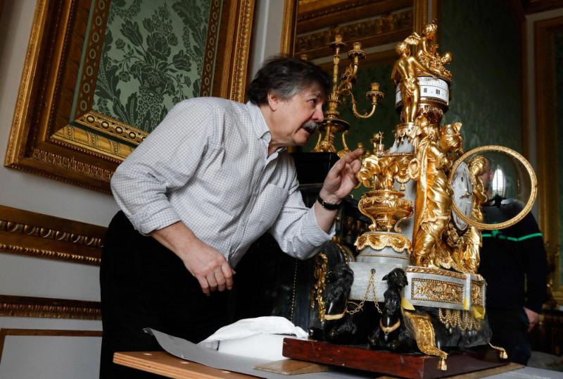 """Versaļas pulksteņmeistars Bernārs Dro novieto Marijas Antuanetes guļamistabā """"Sultānu pulksteni"""" – franču amatnieka Fransuā Remona (1747-1812) meistardarbu."""