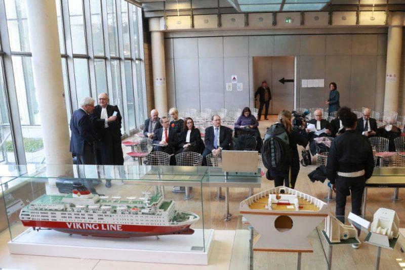 """Atbildētājas šai lietā ir Vācijas kuģubūvētava """"Jos. L. Meyer Werft"""", kurā būvēts prāmis, un Francijas kompānija """"Bureau Veritas"""", kas bija atbildīga par tā drošību un 1994.gadā bija divas reizes to pārbaudījusi, bet vēlāk gadiem ilgi centusies panākt, lai lieta nenonāk tiesā."""