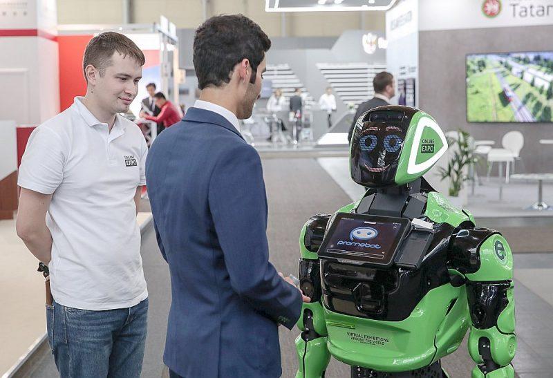 Apmeklētājs sasveicinās ar robotu Hannoveres gadatirgū, kas notika šomēnes.