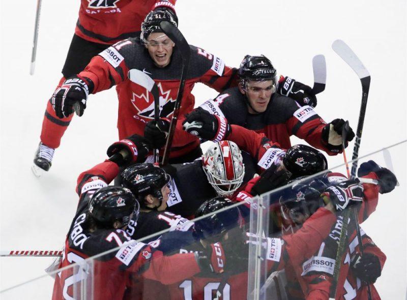 Kanādas izlases hokejisti priecājas pēc uzvaras vārtu guvuma pret Šveici.