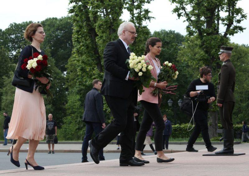 Jaunievēlētais prezidents Egils Levits ar dzīvesbiedri Andru un meitu Indru noliek ziedus pie Brīvības pieminekļa