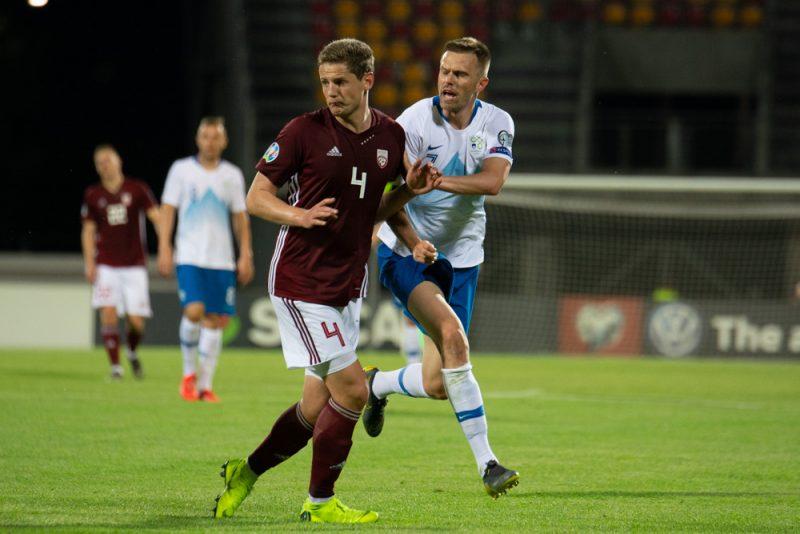 Latvijas izlases kapteinis Kaspars Dubra (no kreisās) spēlē pret Slovēniju.