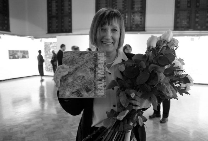 """Latvijas Mākslas akadēmijas Tekstilmākslas katedras vadītāja profesore Aija Baumane 2009. gadā ar ziediem personālizstādes """"Laika zīmes"""" atklāšanā."""