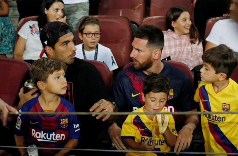 """Luiss Svaress (no kreisās) un Lionels Mesi ar dēliem skatās """"Barcelona"""" spēli."""