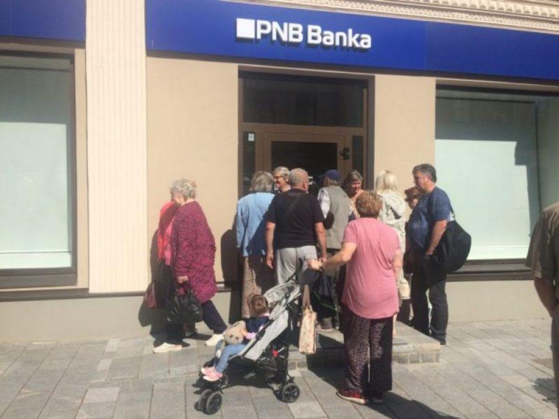 """Cilvēku rinda pie slēgtās """"PNB bankas"""" Daugavpilī."""