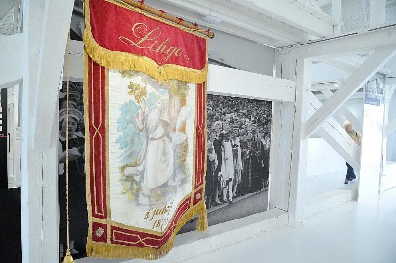 """Skats no izstādes """"Mērijas ceļojums"""". Priekšplānā: arī Latviešu Vispārējo dziesmu svētku relikvija – 1873. gadā darinātais Līgo karogs – ir viena no kultūrvēsturiskajām vērtībām, ko 1944.–1946. gadā nosargāja Mērija Grīnberga. Kopija, Rīgas vēstures un kuģniecības muzejs."""