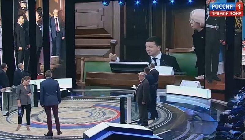 Sarunu šova dalībnieki pievērsušies lielajam ekrānam, lai kopā noskatītos, kā Ukrainas prezidents sit ar āmuriņu.