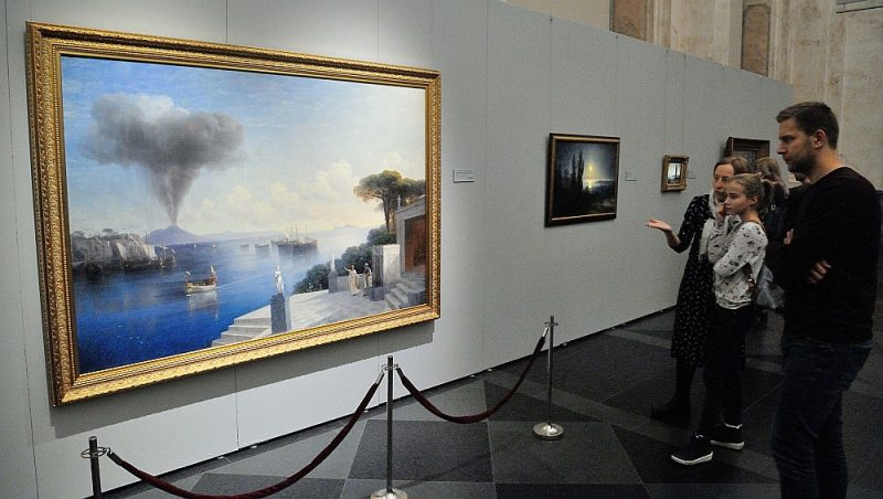 """Liekot uzsvaru uz īpašu koloristisku smalkumu un emocionālās noskaņas niansēm, izstādes veidotāji izvēlējušies prezentēt Ivanu Aivazovski, īpašu uzmanību pievēršot daudzveidīgajiem teatrālajiem gaismas efektiem. Fonā glezna – """"Skats uz Vezuvu dienu pirms vulkāna izvirduma"""" (1885. gads, audekls, eļļa. Igaunijas Mākslas muzejs)."""