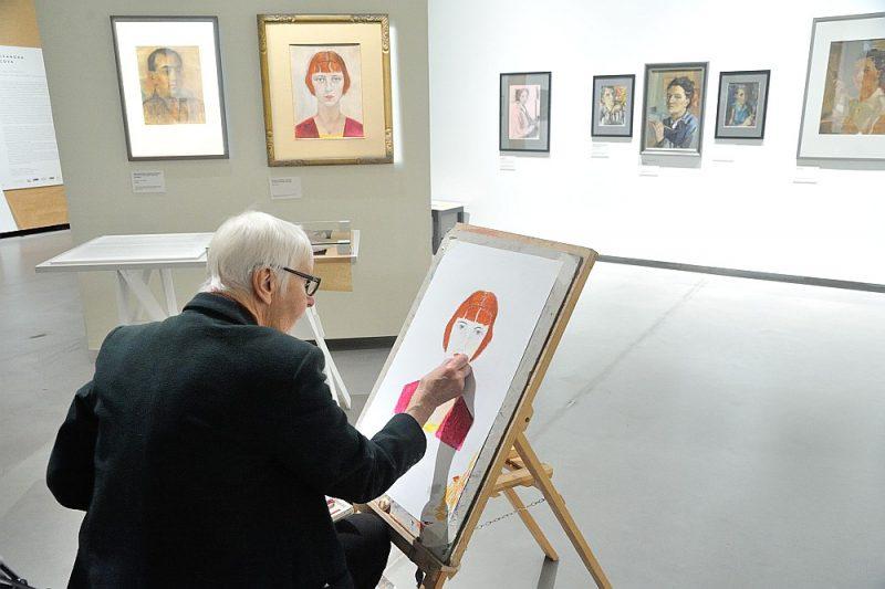 """Aleksandras Beļcovas plašajam radošajam mantojumam veltītā ekspozīcija rosina arī apmeklētājus pašiem iesaistīties mākslas darbu tapšanā. Fonā (pa labi): Aleksandra Beļcova, """"Birutas Ozoliņas portrets"""". Audekls, kartons, eļļa. Privātkolekcija."""
