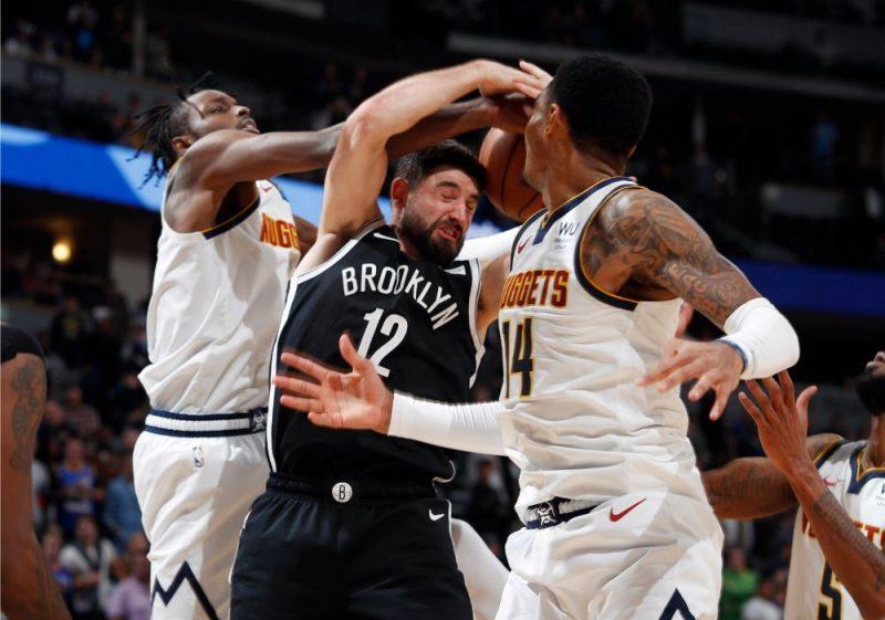 """Kuruca komandas biedrs Džo Heriss (centrā) cīnās ar Denveras """"Nuggets"""" basketbolistiem."""