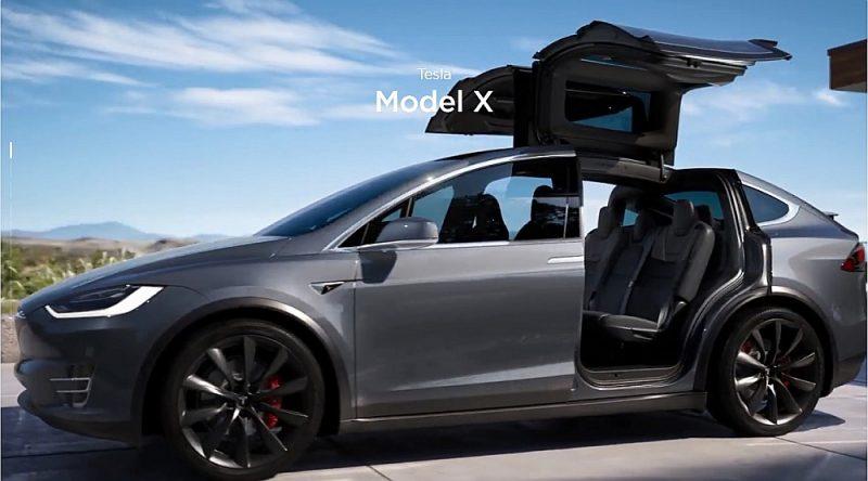 """Elektroauto """"Tesla Model X"""" maksā vismaz 80 tūkstošus eiro (bez PVN). Automašīnas durvis ir tā sauktās """"piekūna spārnu"""" durvis, kas atveras vertikāli."""