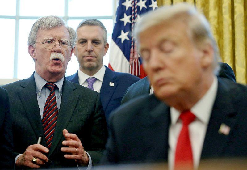 Bijušais nacionālās drošības padomnieks Džons Boltons (no kreisās) apspriežas ar prezidentu Donaldu Trampu Baltā nama Ovālajā kabinetā 2019. gada februārī.