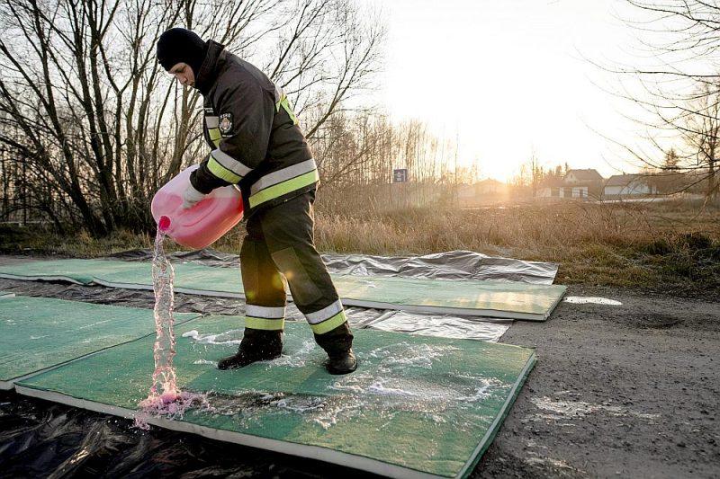 Ugunsdzēsējs 3. janvārī izlaista dezinficējošu šķidrumu uz ceļa Starijuscimovā, Polijā, kur atklāta putnu gripa.