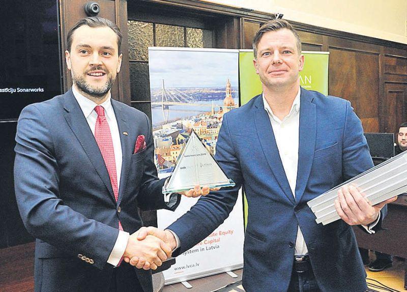 """""""Imprimatur Capital"""" partneris Jānis Jānevičs (no labās) tik tikko spēj saturēt rokās visas piecu investoru grupai piešķirtās balvas par ieguldījumiem """"Sonarworks""""."""